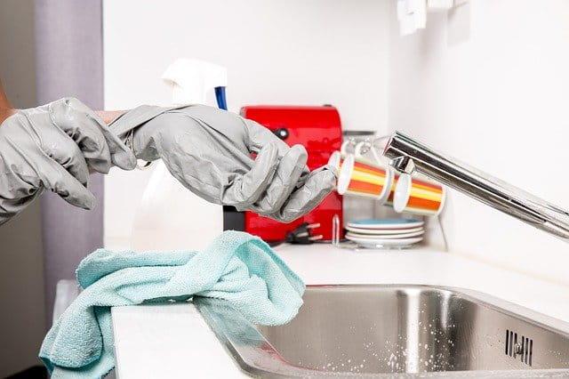 Une personne enfilant ses gants de nettoyage.