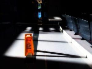Signalisation de sol glissant dans un hall.