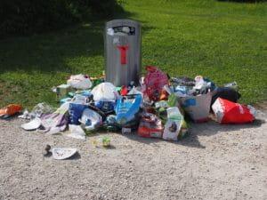 C'est une poubelle pleine, avec des déchets autour.