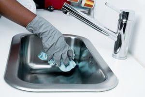 C'est une personne qui nettoie un évier.