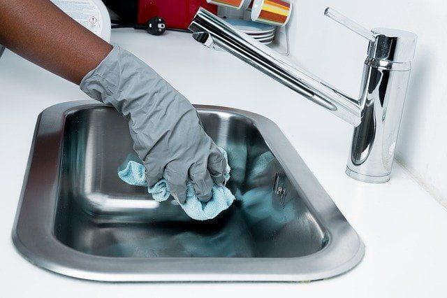 Une personne qui nettoie un évier.