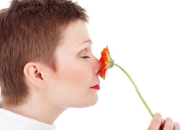 Femme adulte qui sent une fleur