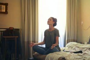 Femme dans une position de méditation sur son lit.